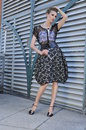Model in designers dress posing outside fashion front of metallic background and holding sunglasses Royalty Free Stock Photography