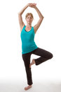 Model doing yoga fitness standing on one leg with her hands clasped together and arms above her head in a pose isolated on white Stock Photography