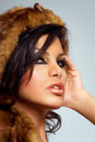 Model in fur wearing brown hat and golden lipstick Royalty Free Stock Photos