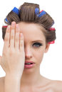 Model hiding her eye pretty with hair curlers Stock Photo