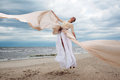 Model jumps with long dress l like a wings at the beach Stock Image
