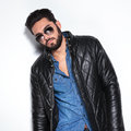 Model in leather jacket and sunglasses posing fashion male studio Royalty Free Stock Photos