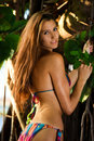 Model posing sexy in front of tropical jungle tree Royalty Free Stock Photo