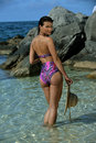 Model posing at tropical location showing back of her swimsuit Royalty Free Stock Photography