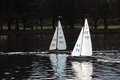 Model racing yachts two on a tranquil park lake in light wind Stock Image
