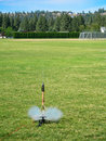 Model rocket launching a in a grassy field Stock Photography