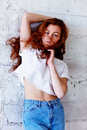 Model tests. Beautiful redhead girl with curly hair.Natural color. Stands with long hair blowing against the light brick Royalty Free Stock Photo