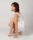 Model in tip toes an image of a gorgeous young a white dress posing on her Royalty Free Stock Photography