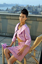 Model wearing couture pink suit posing on the rooftop seductive brunette with city view background Stock Images