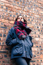 Model wearing scarf and barbour style jacket portrait of a tartan skynny black jeans suede brown ankle boots brick wall as a Royalty Free Stock Photography
