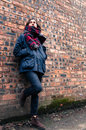 Model wearing scarf and barbour style jacket portrait of a tartan skynny black jeans suede brown ankle boots brick wall as a Royalty Free Stock Photos
