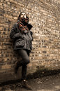 Model wearing scarf and barbour style jacket portrait of a tartan skynny black jeans suede brown boots brick wall as a background Stock Photos