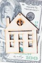 Model of wooden house with dollar bills. House building, loan, real estate, cost of housing or buying a new home concept. Royalty Free Stock Photo