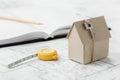 Modelkartonhuis met sleutel en meetlint op blauwdruk De huisbouw, architecturale en bouwontwerpconcept