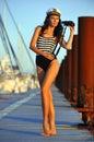 Modello del marinaio in binocolo alla moda della tenuta del costume da bagno e condizione sul pilastro di legno Immagini Stock Libere da Diritti