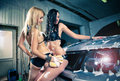 Models at the car wash in garage. Royalty Free Stock Image