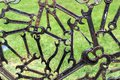 Modern abstract industrial background from welded metal spanners with grass behind.