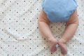 Modern all in one cloth diaper tiny baby feet and legs on a blanket with gender neutral pastel dots baby is wearing a Royalty Free Stock Photo