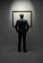 Modern art a young man standing in front a empty frame in a museum Royalty Free Stock Image