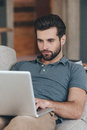 Modern blogger handsome young man using his laptop while sitting on the couch at home Royalty Free Stock Images