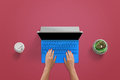 Modern blue laptop on red desk. Woman typing on keyboard. Top view Royalty Free Stock Photo
