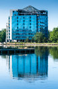 Modern building reflection water almost finished blue facade with white windows in Stock Photos