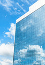 Modern business building over blue sky facade of with reflection of cloudy in the windows Royalty Free Stock Image
