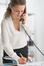 Modern business woman in office talking phone and making notes Royalty Free Stock Images