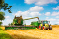 Modern combine at harvest time a john deere and claas tractor and trailer harvesting oil seed rape Stock Photo