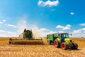Modern combine and tractor at harvest time a john deere a claas trailer Royalty Free Stock Photography