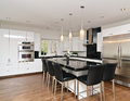 Modern contemporary white kitchen with island granite counter tops stainless steel refrigerator oven and hardwood floors Stock Photo