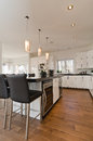 Modern contemporary white kitchen with island granite counter tops wine fridge and hardwood floors Royalty Free Stock Photo