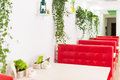Modern design restaurant interior in white and red colors with plants. Royalty Free Stock Photo
