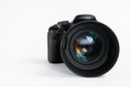 Modern digital photo camera with mm photo lens facing forward Royalty Free Stock Photo