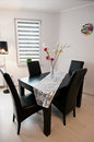 Modern dining room sleek black table leather chairs white walls clock flowers Royalty Free Stock Images