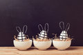 Modern Easter egg decorations with bunny ears on chalkboard. Creative Easter background. Royalty Free Stock Photo