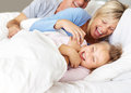 Modern family enjoying themselves on bed Royalty Free Stock Photography