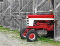 Modern farm tractor in an old shed Royalty Free Stock Photo