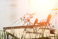 Modern fishing tackle pod with spinning rods and black portable armchairs standing on wooden pier at riverside sunny day Royalty Free Stock Image
