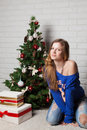Modern girl near christmas tree smiling new year s Stock Photography