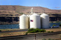 Modern grain elevator a large busy in eastern oregon on columbia river windmills on top of distant hills simi transport and Stock Photography
