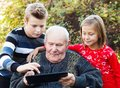 Modern grandfather curious learning from his grandchildren how to use a tablet Stock Photography