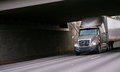 Modern grey semi truck under bridge on interstate highway Royalty Free Stock Photo