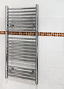 Modern heated towel rail chrome which serves a dual purpose as a radiator and dryer in bathrooms Stock Photos