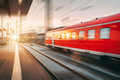 Modern high speed red passenger train moving through railway sta Royalty Free Stock Photo
