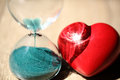 Modern hourglass and red heart with copy space. Royalty Free Stock Photo