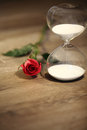 Modern hourglass and red rose with copy space. Royalty Free Stock Photo