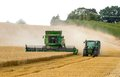 Modern 9780i cts john deere combine harvester cutting crops corn wheat barley working golden field