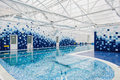 Modern indoor light swimming pool decorated with blue tiles Royalty Free Stock Photo