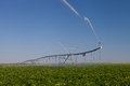 Modern irrigation pivot agricultural watering a crop of potatoes Stock Images